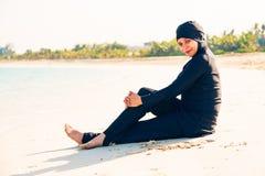 Ung kvinna som bär Burkini sammanträde vid stranden Royaltyfri Foto