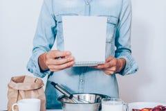 Ung kvinna som bär den blåa skjortan som lagar mat fruktkakan fotografering för bildbyråer