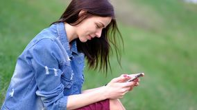 Ung kvinna som bär det blåa stilfulla jeansomslaget genom att använda hennes telefon eller smartphone, smsa eller läsning, ultrar