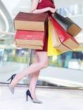 Ung kvinna som bär färgrika pappers- påsar som går, i att shoppa mal Arkivfoton