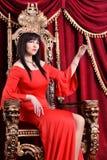 Ung kvinna som bär rött klänning- och kronasammanträde i tappningstol Arkivfoton
