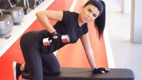 Ung kvinna som böjer muskler med hanteln på bänk i idrottshall lager videofilmer