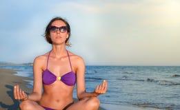 Ung kvinna som bara mediterar på stranden Arkivbilder