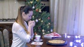 Ung kvinna som ber för målsammanträde på tabellen på bakgrund av julgarneringar lager videofilmer