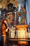 Ung kvinna som ber i en kyrka arkivbild