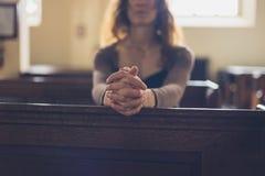 Ung kvinna som ber i kyrka Arkivbilder