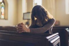 Ung kvinna som ber i kyrka arkivfoto