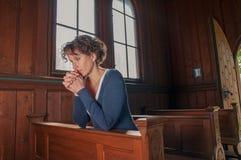 Ung kvinna som ber i kyrkan arkivfoto