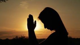 Ung kvinna som ber i skogen på solnedgången stock video