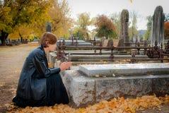 Ung kvinna som ber på graven i kyrkogård i nedgång Arkivbild