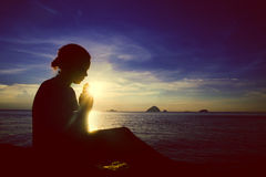 Ung kvinna som ber solnedgång över havbegreppet Royaltyfria Foton