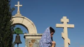 Ung kvinna som ber till guden med knäppte fast händer, stenkors, religiöst symbol arkivfilmer