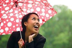 Ung kvinna som beskyddar från regn under paraplyet Royaltyfri Fotografi