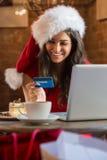 Ung kvinna som betalar hennes räkning i en bärande julhatt för kafé royaltyfri bild