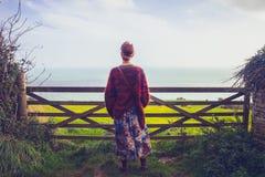 Ung kvinna som beundrar havssikt vid det lantliga staketet Arkivbild