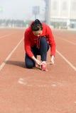 Ung kvinna som binder sportskon Arkivbilder