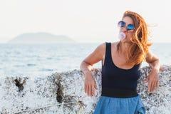 Ung kvinna som blåser bubbelgum Arkivbild