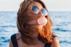 Ung kvinna som blåser bubbelgum Arkivfoton