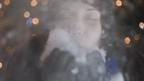 Ung kvinna som blåser snöflingor från hennes händer som står vid julgranen Berömbegrepp för lyckligt nytt år som är utomhus- arkivfilmer