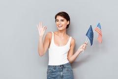Ung kvinna som blinkar och rymmer flaggor Royaltyfri Bild