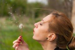 Ung kvinna som blåser på maskrosen Royaltyfri Foto