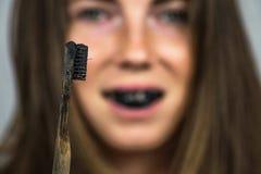 Ung kvinna som borstar hennes tänder med en svart tanddeg med aktivt kol och svarttandborsten på vit bakgrund arkivfoton
