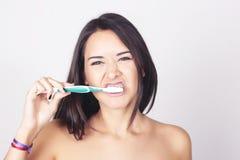 Ung kvinna som borstar hennes tänder som isoleras över vit bakgrund Royaltyfri Fotografi