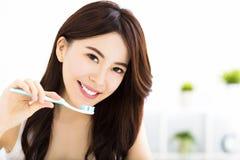 Ung kvinna som borstar tänder i morgonen fotografering för bildbyråer