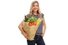 Ung kvinna som bär en påse av livsmedel Royaltyfri Fotografi