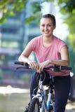 Ung kvinna som cyklar bredvid floden i stads- inställning Royaltyfri Bild