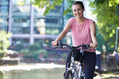 Ung kvinna som cyklar bredvid floden i stads- inställning Royaltyfria Foton
