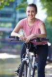 Ung kvinna som cyklar bredvid floden i stads- inställning Arkivfoto