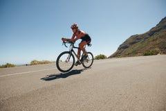Ung kvinna som cyklar på landsvägen Royaltyfri Foto
