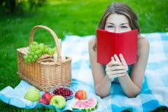 Ung kvinna som döljer hans framsida bak boken Royaltyfria Foton