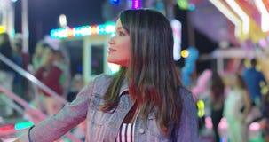 Ung kvinna som dagdrömmer på en funfair arkivfilmer