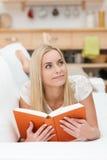Ung kvinna som dagdrömmer, som hon läser arkivbilder