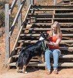 Ung kvinna som daltar hunden Arkivbilder