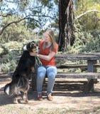 Ung kvinna som daltar hunden Royaltyfria Foton