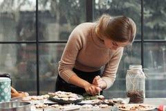 Ung kvinna som dekorerar bakelse på kök Arkivbild