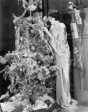 Ung kvinna som dekorerar en julgran (alla visade personer inte är längre uppehälle, och inget gods finns Leverantörgarantitha Arkivbild