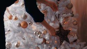 Ung kvinna som dekorerar julgranen med stjärnan Förberedelse för nytt år, slut upp arkivfilmer