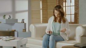 Ung kvinna som direktanslutet shoppar, genom att använda bankrörelseservice på minnestavlaPC lager videofilmer
