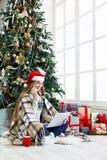 Ung kvinna som direktanslutet shoppar i inre hemtrevlig jul Arkivfoton