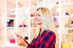 Ung kvinna som direktanslutet shoppar med den minnestavladatoren och kreditkorten arkivbilder