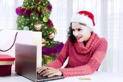 Ung kvinna som direktanslutet shoppar på jultid royaltyfria bilder
