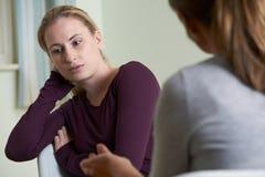 Ung kvinna som diskuterar problem med lägerledaren Royaltyfri Bild