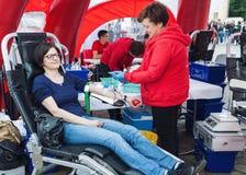 Ung kvinna som donerar blod Arkivfoto