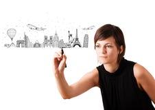 Ung kvinna som drar berömda städer och landmarks på whiteboard Royaltyfri Fotografi