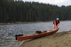 Ung kvinna som drar hennes kajak på en kust för regnet royaltyfria foton