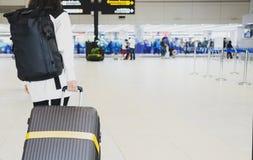 Ung kvinna som drar resväskan i flygplatsterminal Handelsresande för ung kvinna i internationell flygplats med ryggsäckinnehavres arkivfoto